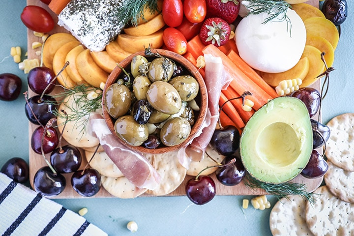 An easy summer crudite platter with sliced veggies, seasonal fruit, creamy cheeses and fresh herbs. Basically summer on a plate!